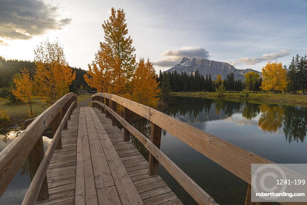 Bridge over Cascade Pond with Mount Rundle on horizon in Autumn, Banff National Park, Alberta, Canada
