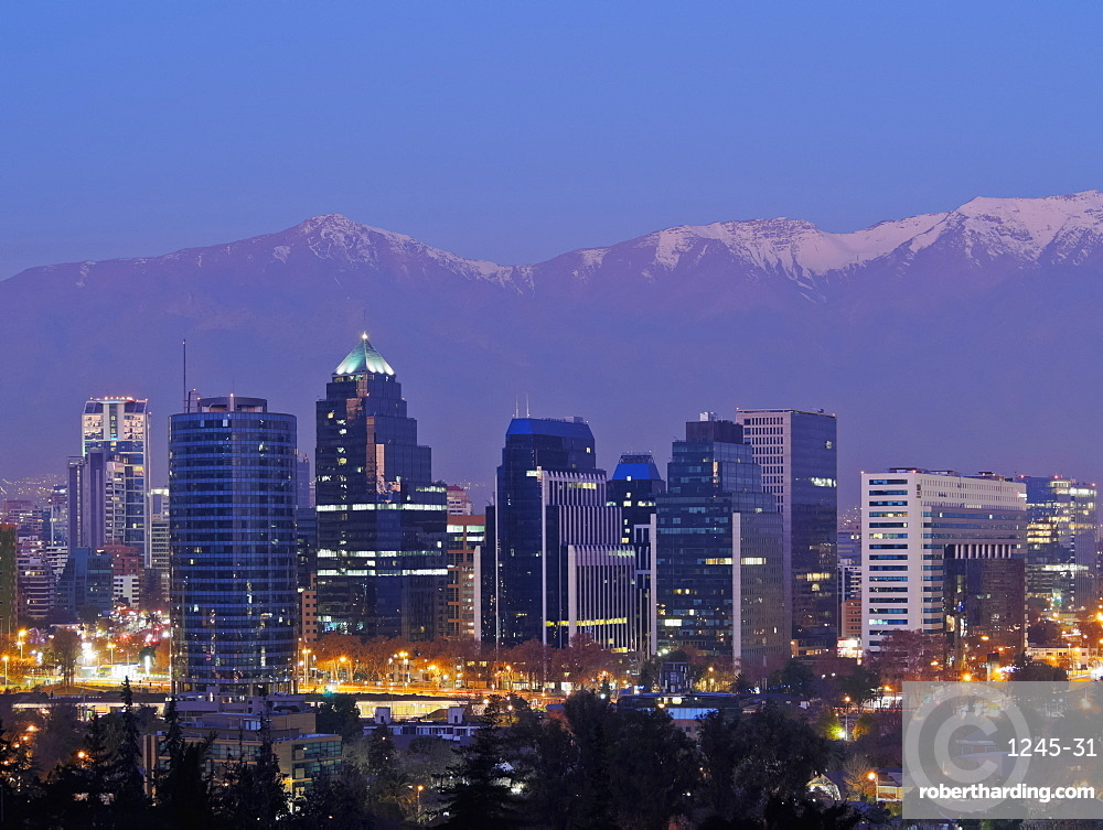 Twilight view from the Parque Metropolitano towards the high rise buildings in the financial sector, and snow covered mountains behind, Santiago, Chile, South America