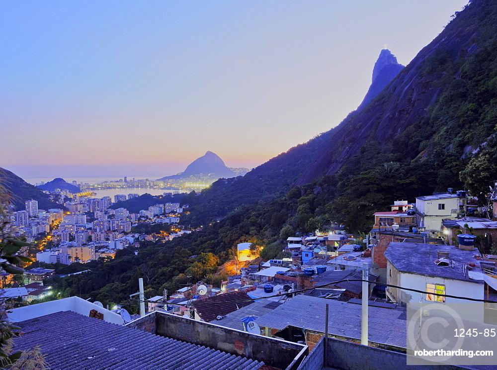 Twilight view of the Favela Santa Marta with Corcovado and the Christ statue behind, Rio de Janeiro, Brazil, South America