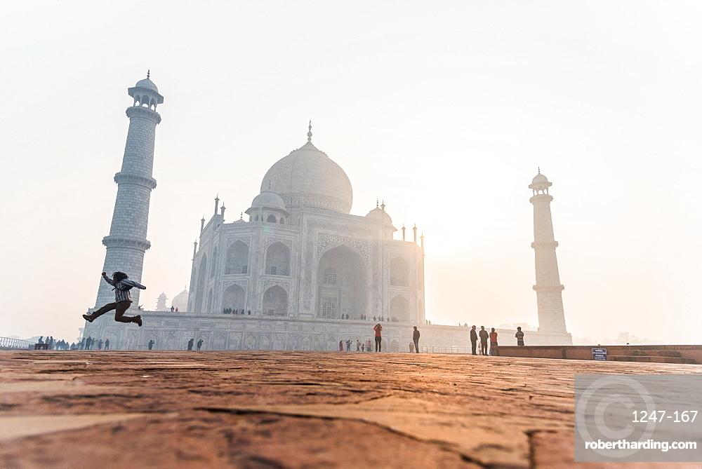 A man jumps as the sun rises behind the Taj Mahal, UNESCO World Heritage Site, Agra, Uttar Pradesh, India, Asia