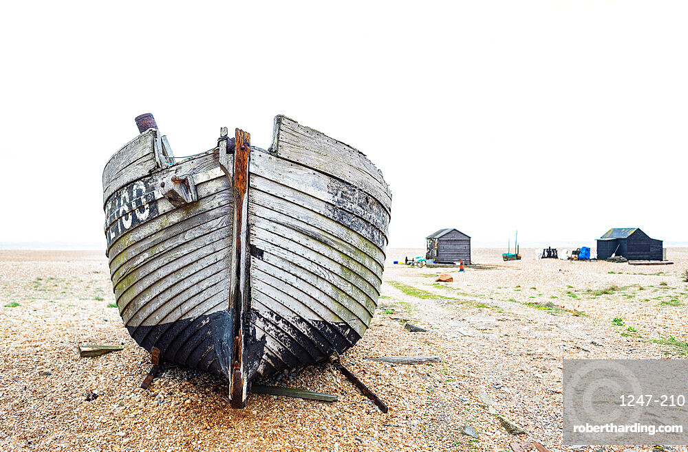 March 2019, Dungeness, Kent, England - The old fishing boat lies on the beach.with fishermans huts inthe background