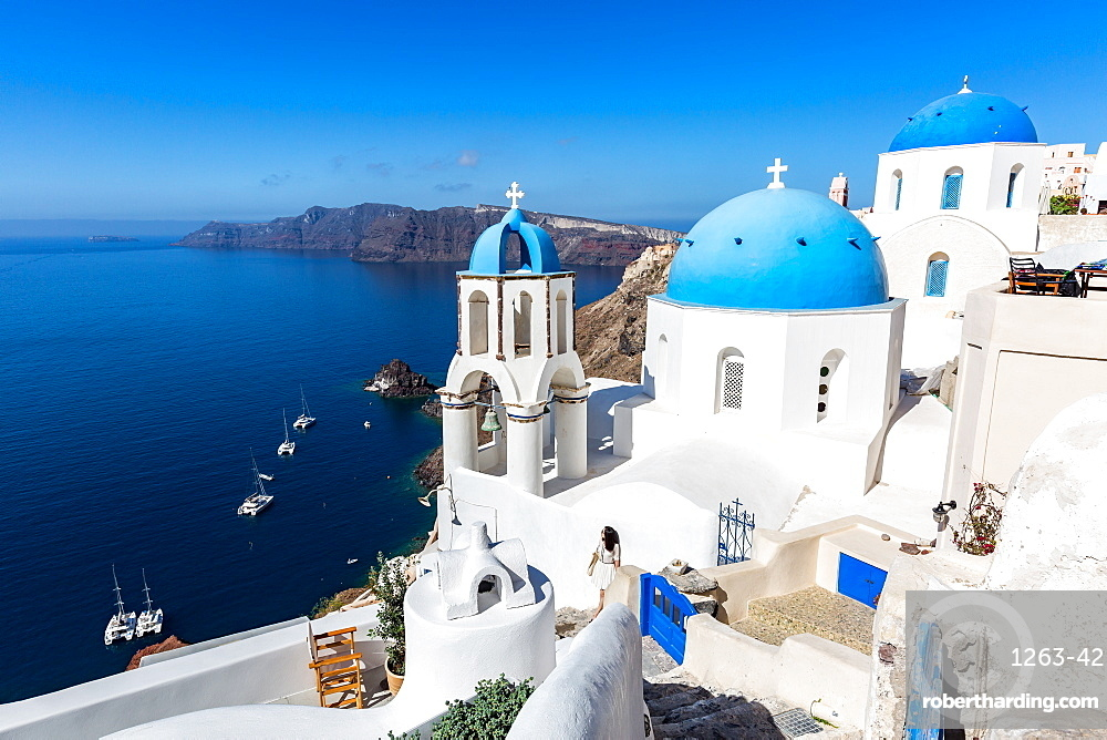 White washed stone buildings and the blue cupolas of a church in Oia, Santorini, Cyclades, Greek Islands, Greece, Europe