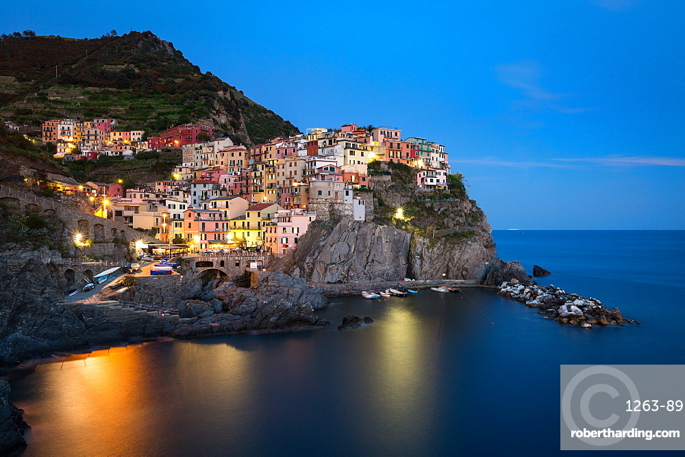 A long exposure at blue hour as the lights come on in the colourful town of Manarola, Cinque Terre, UNESCO World Heritage Site, Liguria, Italy, Europe