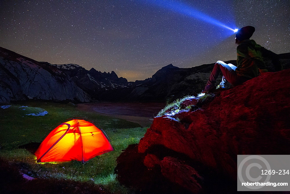 A person looks at stars near his red tent, Unterer Segnesboden, Flims, District of Imboden, Canton of Grisons (Graubunden), Switzerland, Europe