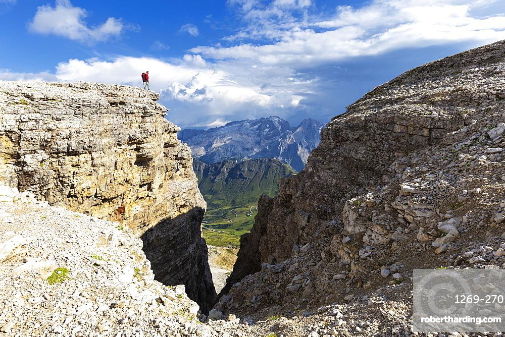 Hiker looks towards Marmolad, Piz Pordoi, Pass Pordoi, Fassa Valley, Trentino, Dolomites, Italy, Europe