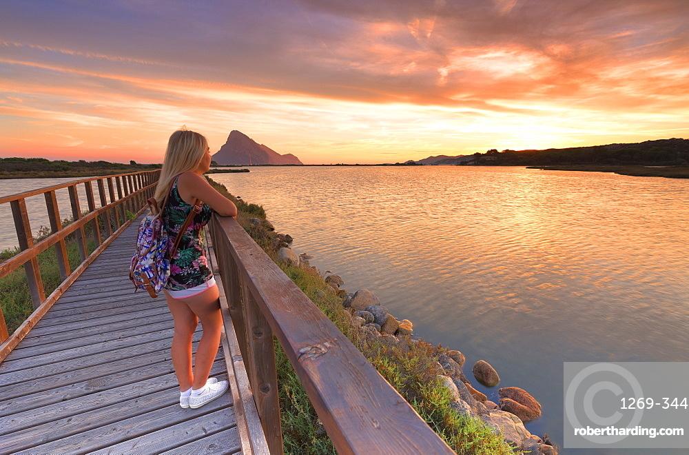 A girl looks at sunrise from a walkway, Porto Taverna, Loiri Porto San Paolo, Olbia Tempio province, Sardinia, Italy, Mediterranean, Europe
