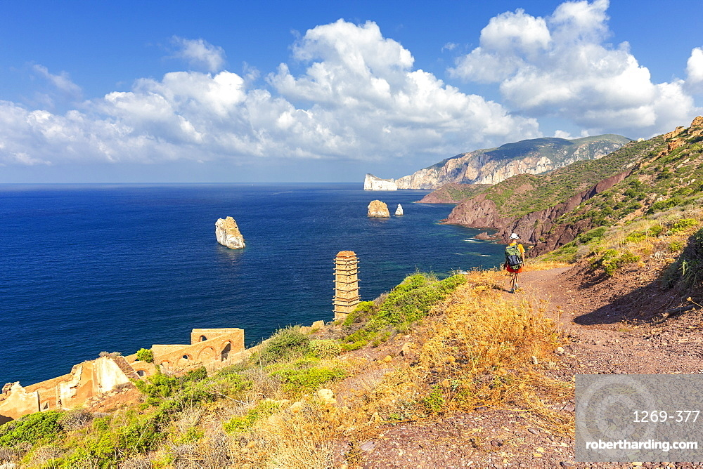 A tourist walks on a path to Laveria Lamarmora, Nebida, Iglesias, Sud Sardegna province, Sardinia, Italy, Mediterranean, Europe