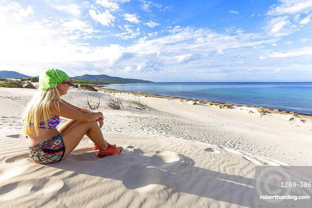 Young girl looks at the sea from a sand dune, Is Arenas Biancas, Teulada, Cagliari province, Sardinia, Italy, Mediterranean, Europe
