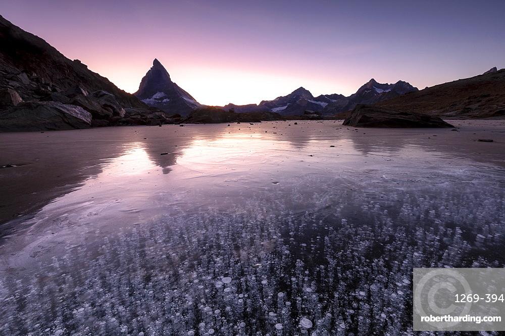 Frozen Riffelsee lake by Matterhorn at sunset in Switzerland, Europe