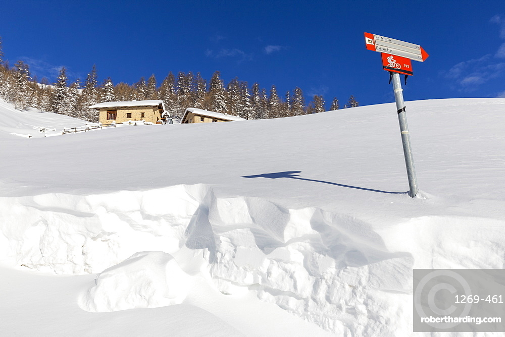 Traditional huts with trekking signal in winter, Livigno, Valtellina, Lombardy, Italy, Europe