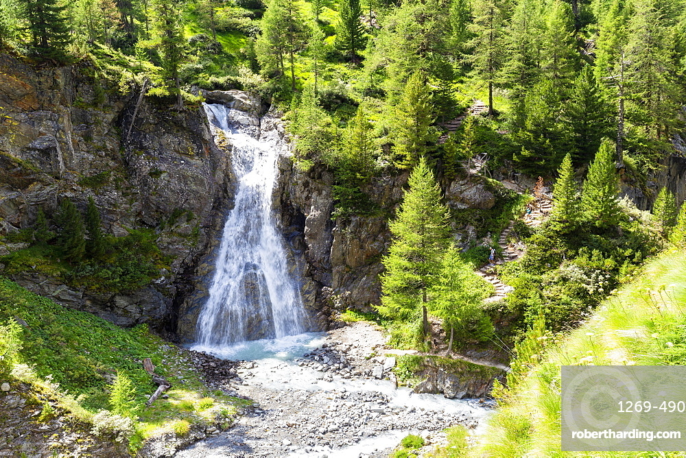 Waterfall of Val Nera with tourist on the path, Livigno, Valtellina, Lombardy, Italy, Europe