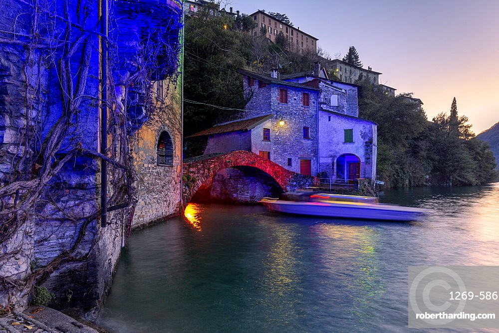 Boat in motion under the illuminated Nesso bridge, Lake Como, Lombardy, Italian Lakes, Italy, Europe