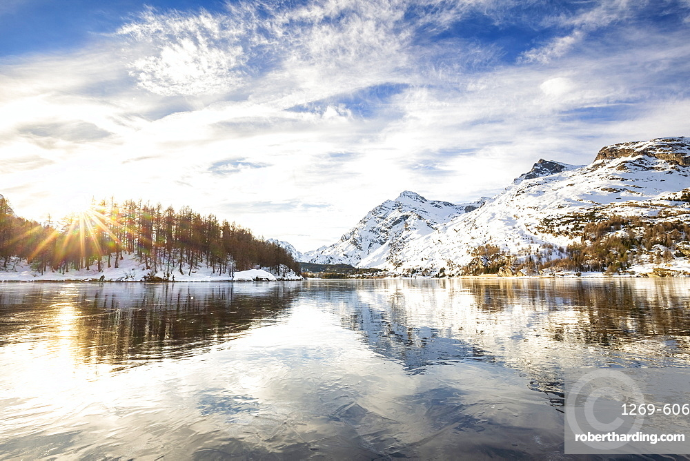 The sun illuminates the icy surfaces of Lake Sils, Engadine Valley, Graubunden, Swiss Alps, Switzerland, Europe