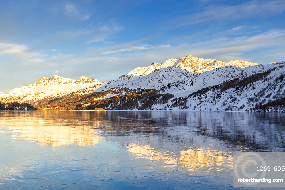 Mountains illuminated by sun at sunset reflected on the icy surfaces of Lake Sils, Engadine, Graubunden, Switzerland, Europe