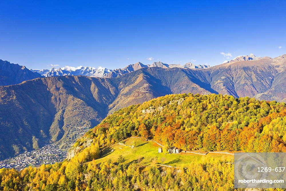 Small group of huts in autumn colors with view over the mountains, Valtellina, Lombardy, Italy, Europe