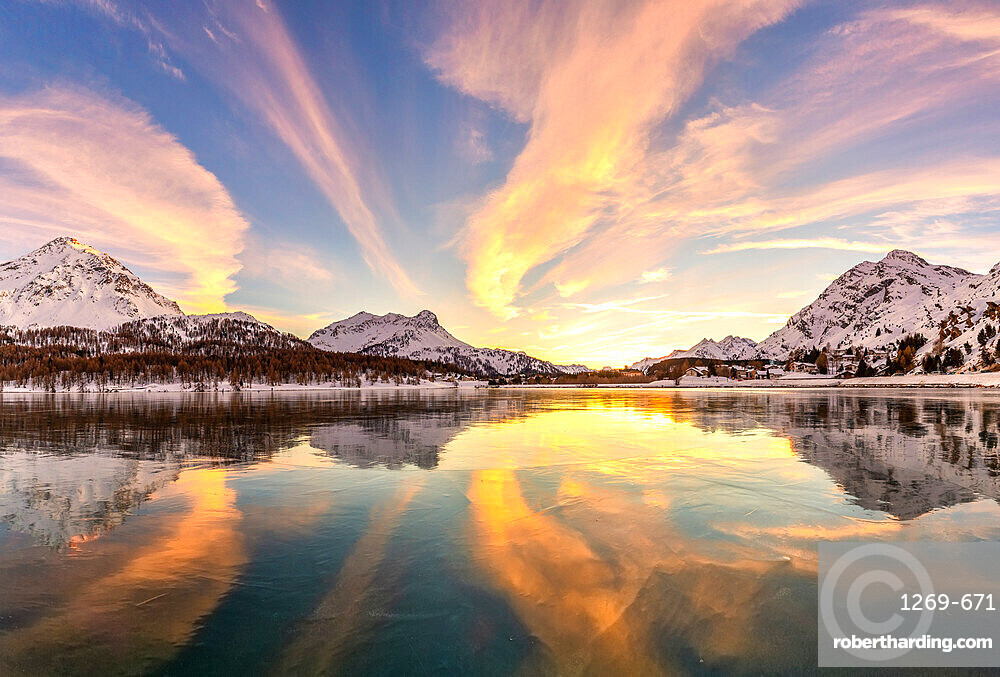 Colors of sunset reflected on the icy surface of Lake Sils, Engadine Valley, Graubunden, Switzerland, Europe