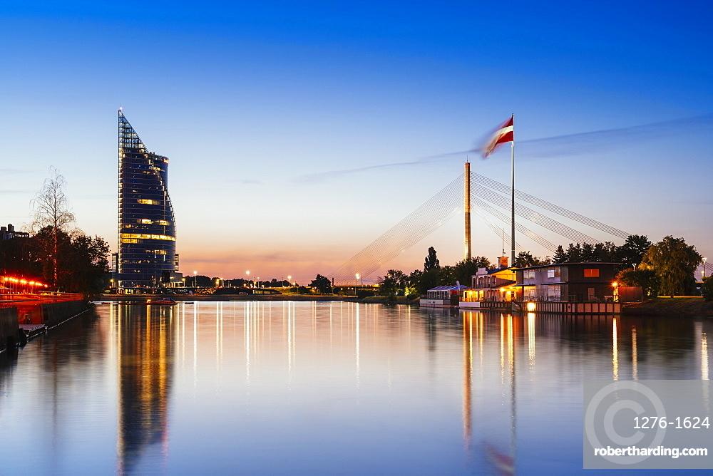 Suspension bridge with huge Latvian flag from AB dam at sunset, Riga, Latvia, Europe