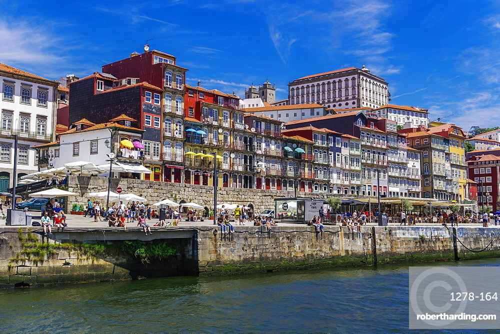 Traditional waterfront houses in the Ribeira district on the Douro River with crowd on river bank, Porto, Portugal, Europe