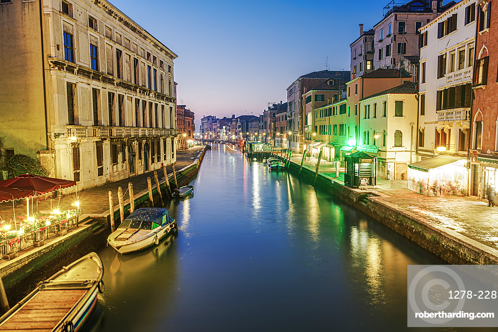 Evening canal view of low rise traditional buildings and wooden wharf pilings with moored boats, Venice, UNESCO World Heritage Site, Veneto, Italy, Europe