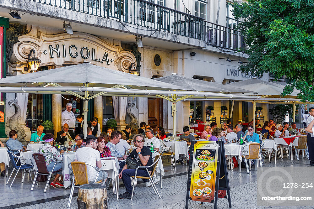 Historic Cafe Nicola entrance with art deco facade and seated customers at outdoor tables in Rossio Square, Lisbon, Portugal, Europe