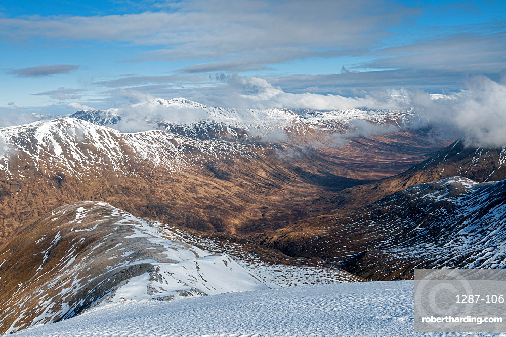 Looking down into Fionngleann in winter from Brothers Ridge in Kintail with the hills of Wester Ross in distance