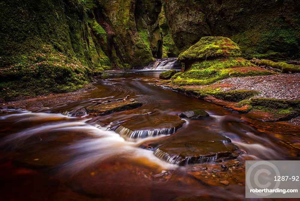 The gorge at Finnich Glen, known as Devils Pulpit near Killearn Scotland. The river is a red colour from the minerals and rocks