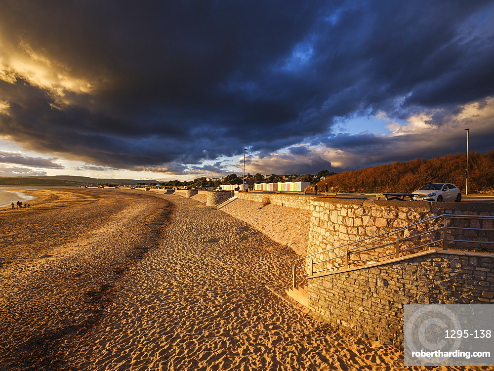 Under dramatic clouds, strong warm sunlight illuminates the beach and sea defences on the sea front at Exmouth, Devon, England, United Kingdom, Europe