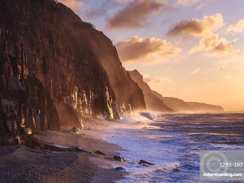 Spray from a storm blows up the cliffs at dawn in the seaside town of Sidmouth, Devon, England, United Kingdom, Europe