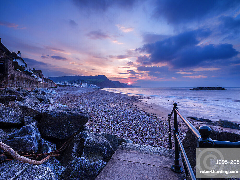 Sunrise looking along the beach at the picturesque seaside town of Sidmouth, Devon, UK