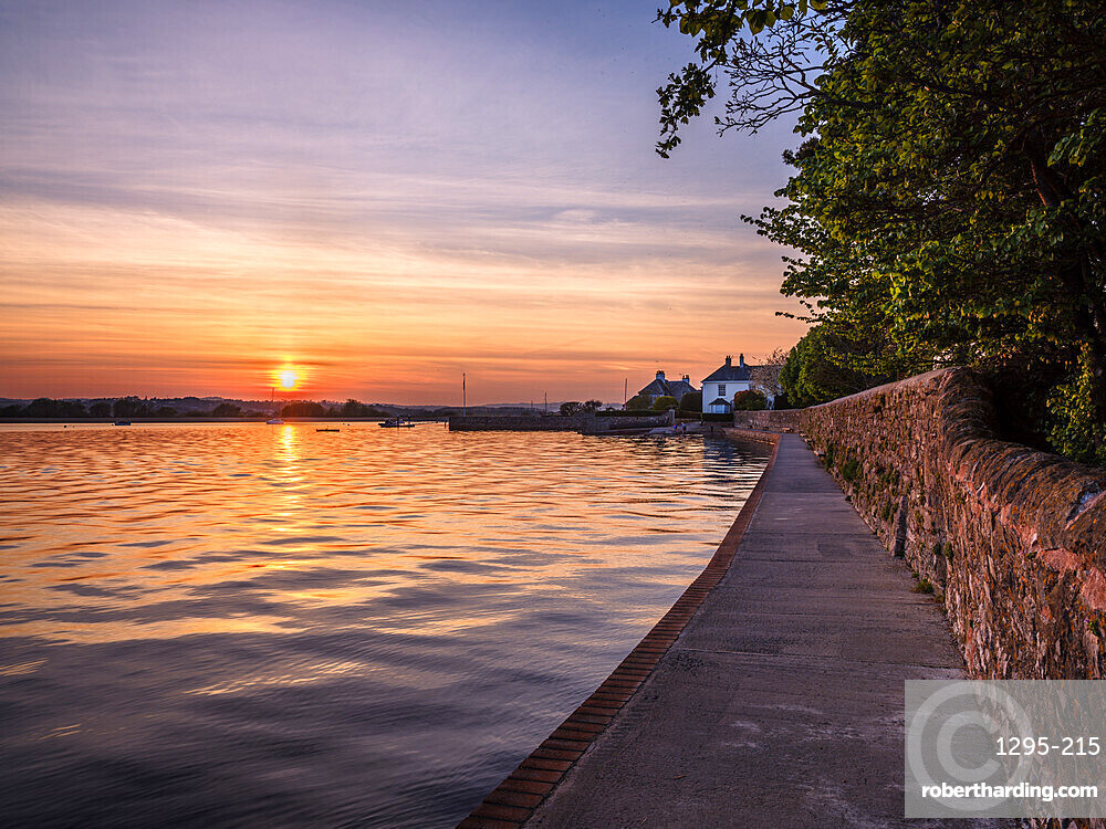 High tide sunset on The Goat Walk with a mirror calm River Exe at Topsham, Devon, UK