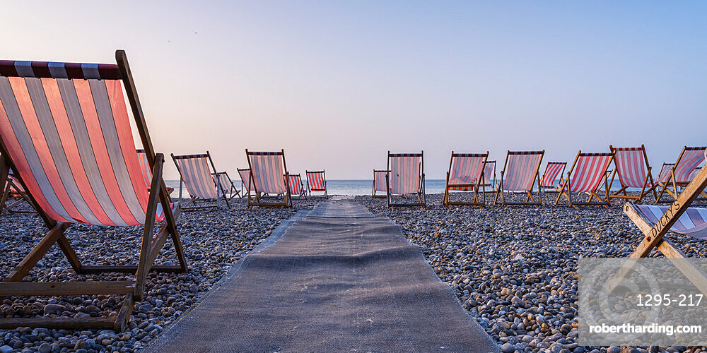 Dckchairs on the popular pebbled beach at Beer near Seaton, Devon, UK