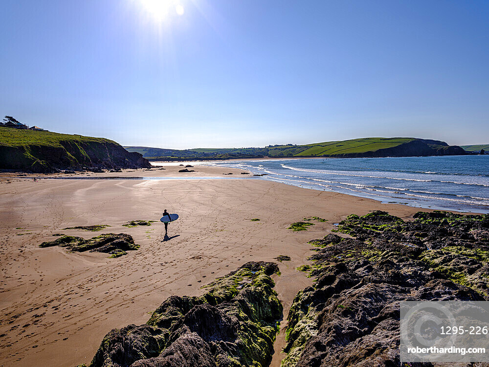 A surfer walks towards his session on sunny morning at Bigbury-on-Sea, Devon, UK.