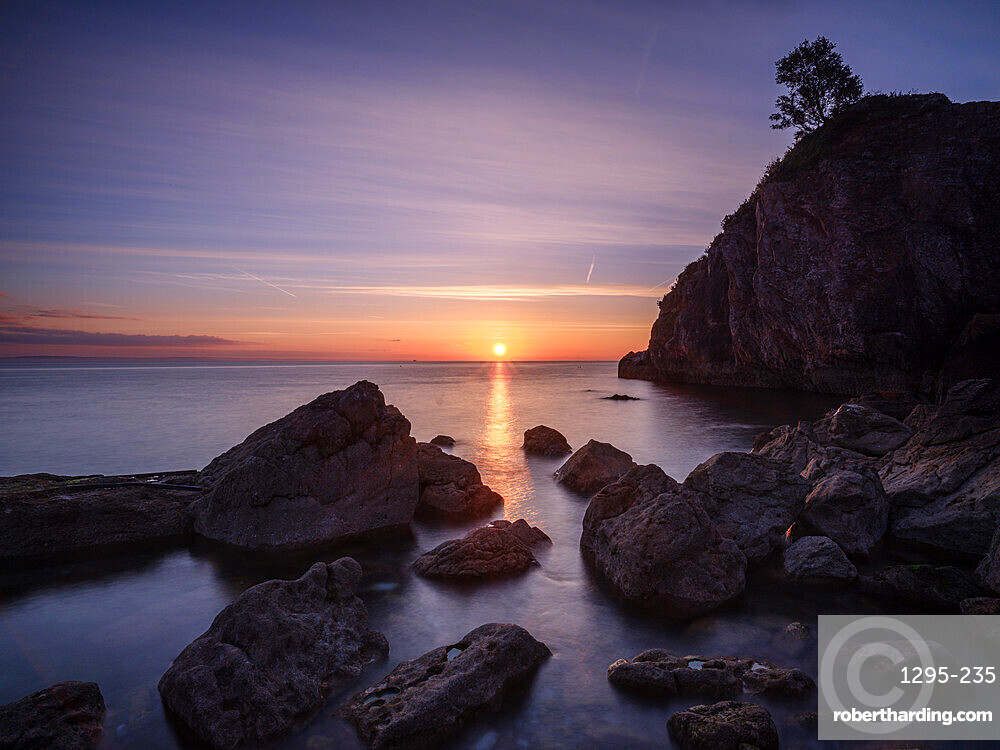A colourful sunrise over Torbay with warm light on rocks, Babbacombe, Torquay, Devon, UK