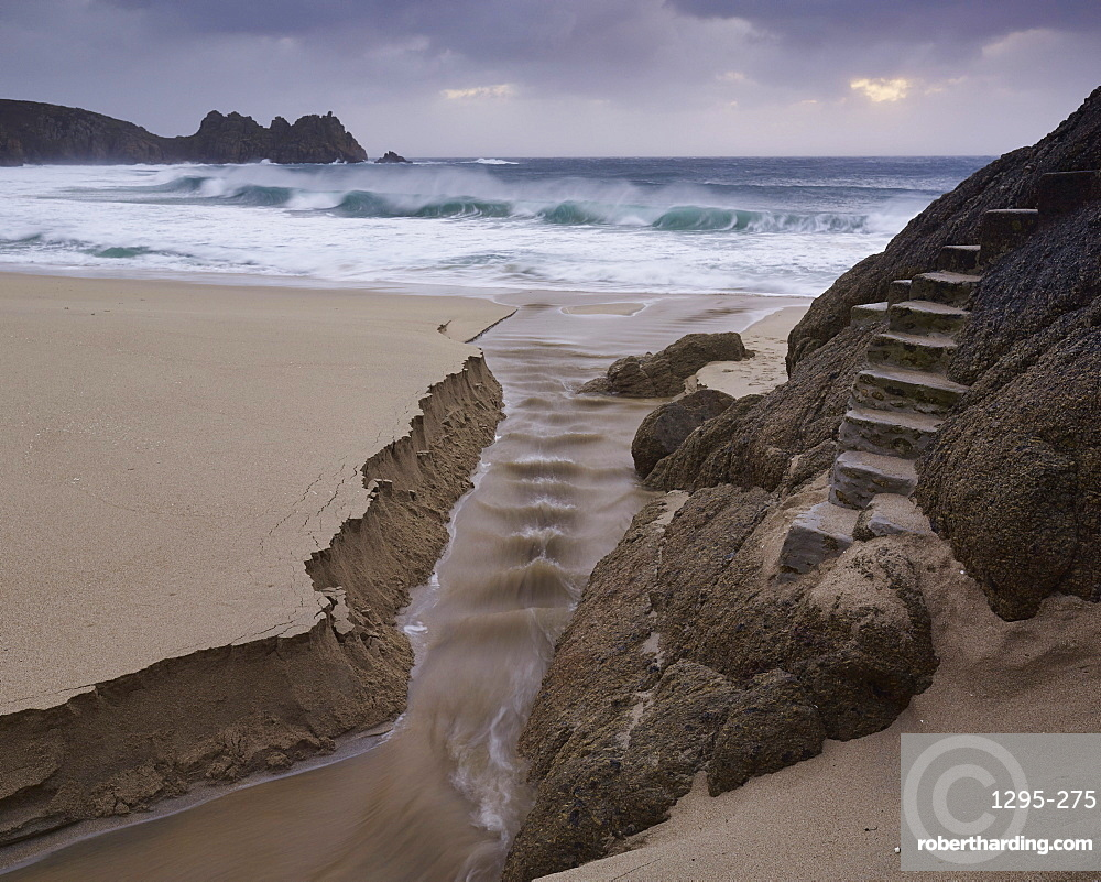 Stormy conditions on the beach looking out towards Logan Rock at Porthcurno, Cornwall, England, United Kingdom, Europe