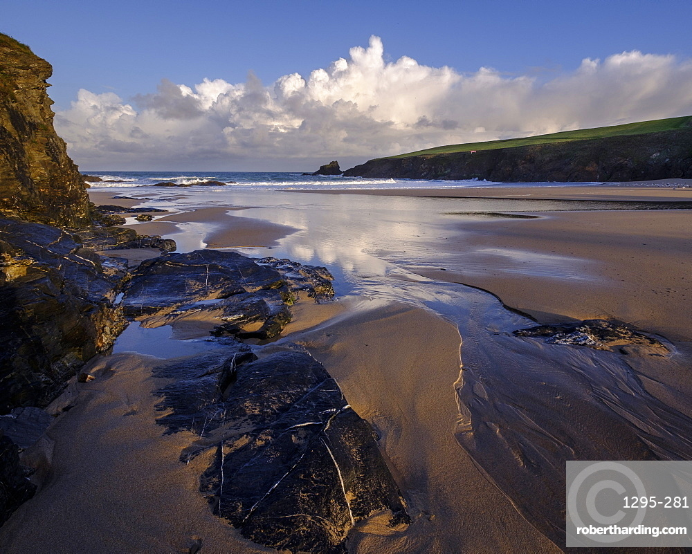 Atlantic clouds reflect dawn light onto the wet sands and rocks of Trevone, near Padstow, Cornwall, England, United Kingdom, Europe