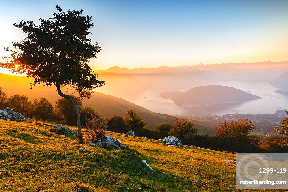 Iseo Lake and Monte Isola at sunset with fog in autumn season, Brescia Province, Lombardy, Italy, Europe