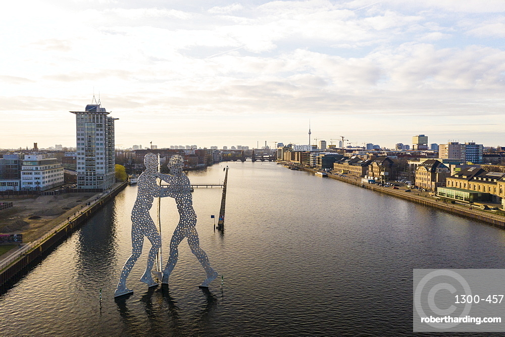 View of the Molecule Man statue in Treptow with Spree River and Berlin skyline in the background, Berlin, Germany, Europe