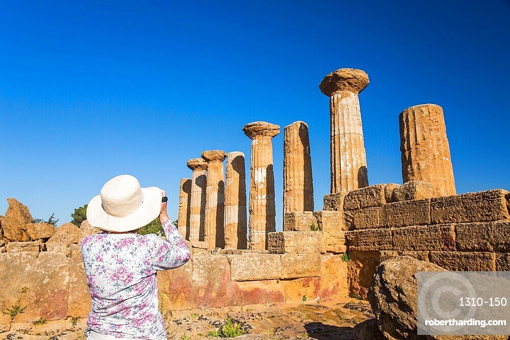 Visitor photographing the Temple of Heracles, aka Hercules, in the UNESCO listed Valley of the Temples, Agrigento, Sicily, Italy