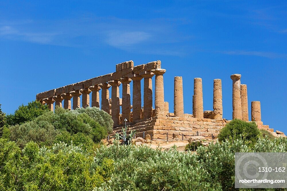 View over trees to the hilltop Temple of Hera, aka Juno, in the UNESCO listed Valley of the Temples, Agrigento, Sicily, Italy