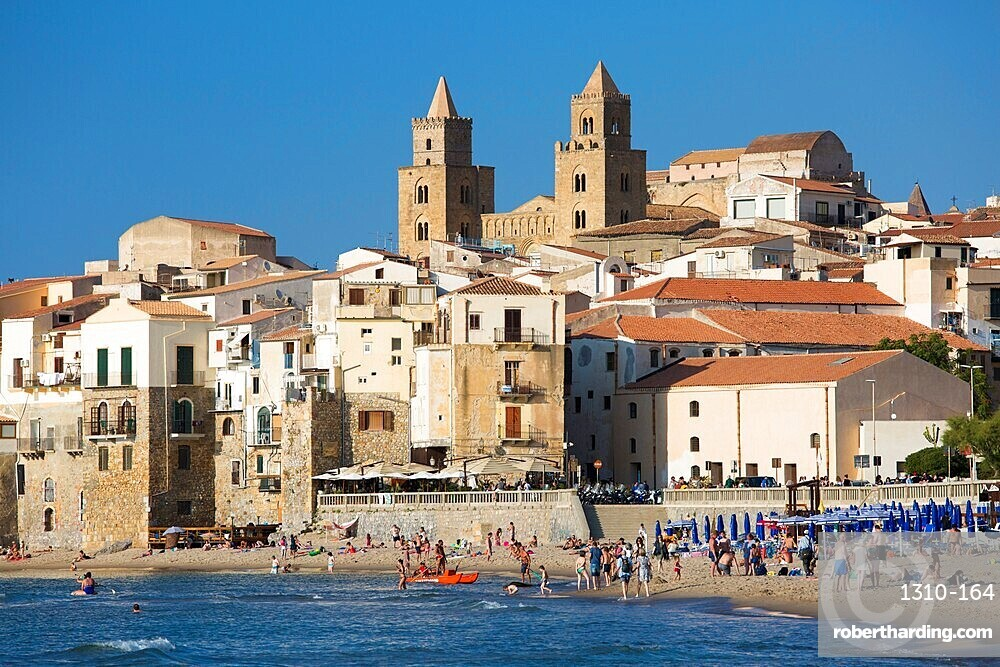 View from beach along water's edge to the town and UNESCO listed Arab-Norman cathedral, Cefalu, Palermo, Sicily, Italy