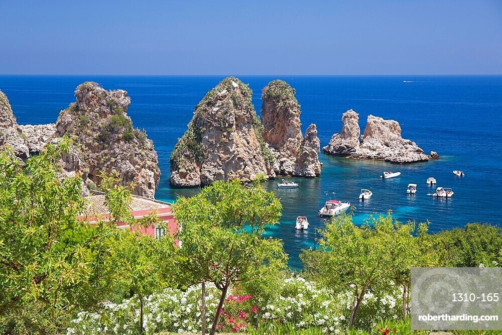 View from hillside over tranquil cove to the Faraglioni, a series of offshore rock stacks, Scopello, Trapani, Sicily, Italy