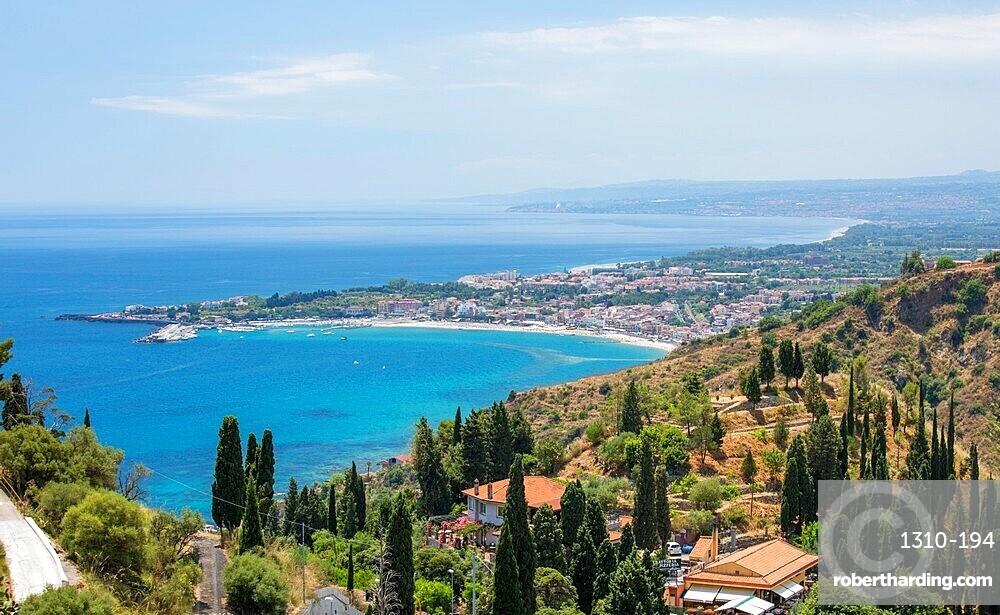 View over the turquoise waters of the Bay of Naxos to distant Giardini-Naxos, Taormina, Messina, Sicily, Italy