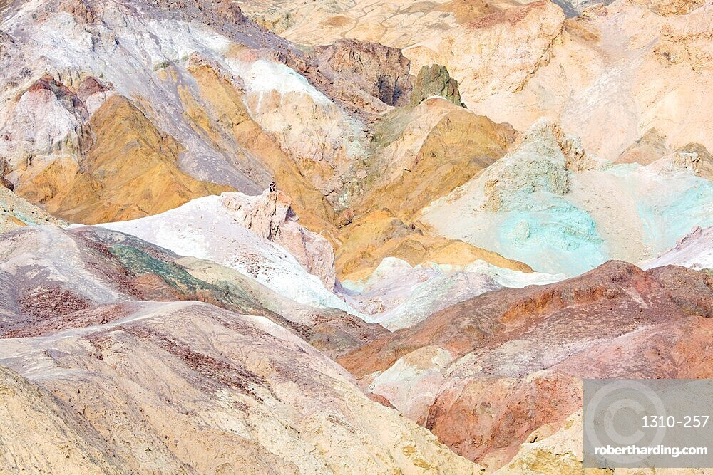 Visitor dwarfed by landscape of colourful rocks, Artist's Palette, Furnace Creek, Death Valley National Park, California, USA