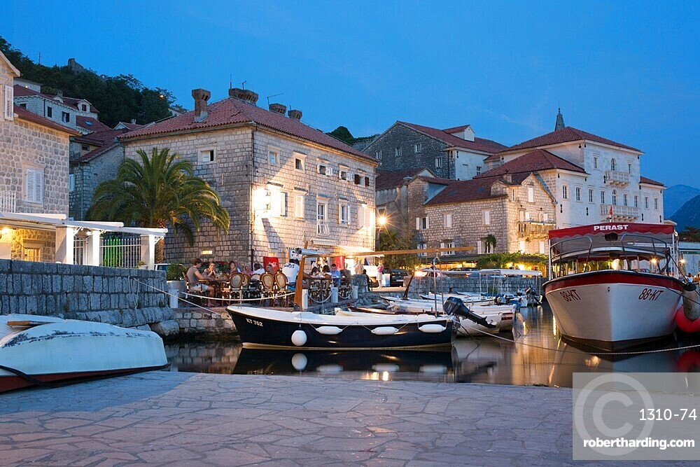 View across the illuminated harbour to waterfont mansions overlooking the Bay of Kotor, dusk, Perast, Kotor, UNESCO World Heritage Site, Montenegro, Europe