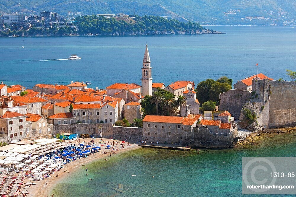 View over crowded beach to the Old Town (Stari Grad), and Budva Bay, Budva, Montenegro, Europe