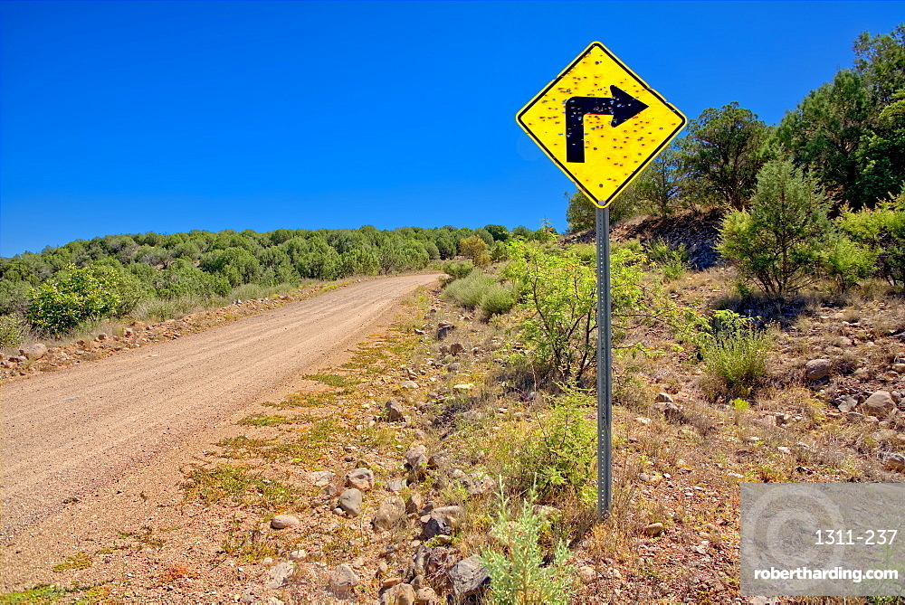 A sign along Forest Service Road 492 that has been shot up by reckless gunfire. Located in Prescott National Forest Arizona.