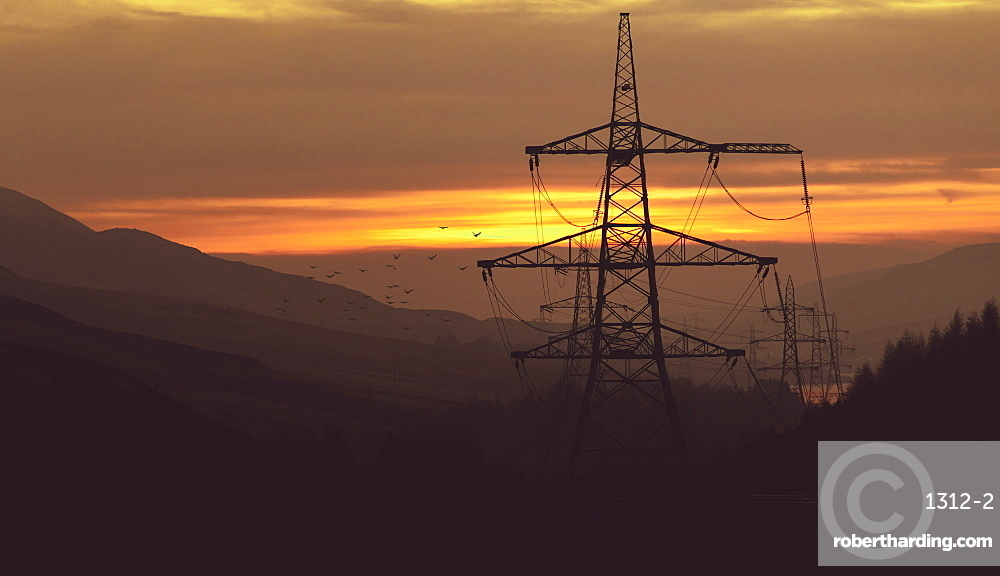 Striking pylons run through a hazy sunset in the Peak District, South Yorkshire, Yorkshire, England, United Kingdom, Europe