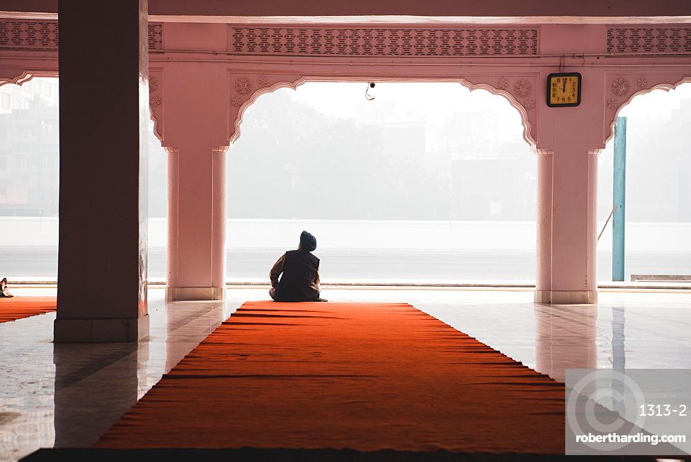 A man contemplates at Gurudwara Santokhsar Temple, Amritsar, Punjab, India, Asia