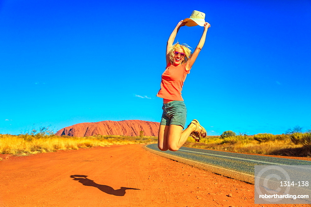 Happy tourist woman holding an hat jumps at Uluru Ayers Rock in Uluru-Kata Tjuta National Park. Lifestyle traveler enjoying in Australian outback Red Centre. Tourism in Northern Territory, Central Australia