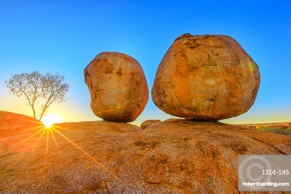 Sunset light rays at Devils Marbles, the Eggs of mythical Rainbow Serpent, at Karlu Karlu (Devils Marbles) Conservation Reserve. Outback, Red Centre, Northern Territory, Australia, Pacific